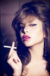 Primer plano de una mujer fumando un cigarrillo.