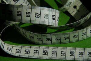 Detalle de cintas métricas de modista sobre mesa verde
