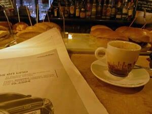 Mesa de cafetería con taza de café, cruasanes y periódico