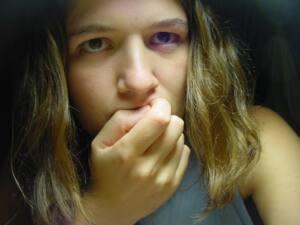 Foto de una muchacha nerviosa llevándose la mano a la boca