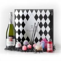 Caja con botella de cava, velas rosas, 2 huevos Tenga, crema de masaje rosa y sales de baño.