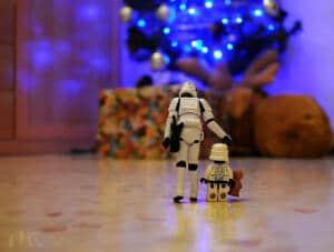 """Muñeco de las fuerzas imperiales de Star wars, de espaldas con su """"hijo"""" otro muñeco de las fuerzas imperiales de lego, caminando hacia unos regalos"""