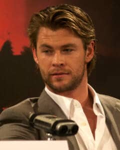 Foto de Chris Hemsworth con el pelo corto, camisa blanca y chaqueta marrón