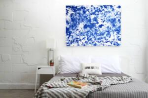 Lienzo azul pintado con love is art kit como cabecero de una habitación