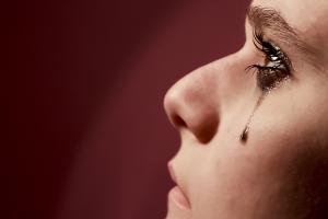 Perfil de una mujer, con una lágrima negra por el rímel , cayéndose por la mejilla