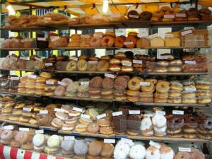Estanterías llenas con donuts de distinto sabor: glaseados, chocolate...