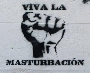 """Grafitti en el que se ve un puño cerrado con la inscripción: """"Viva la masturbación""""."""