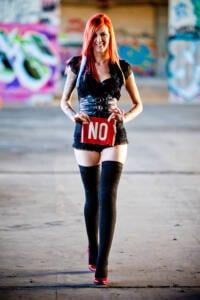 Chica pelirroja con minifalda, medias negras hasta el muslo con un cartel en el que se lee: NO