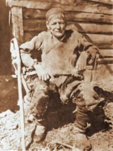 Mujer con ropa de hombre, sentada a la puerta de una cabañaentada e