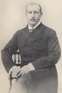 Foto en blanco y negro donde se muestra a Jorge sentado como de medio lado en una silla. Se observa el bigote fino y alargado