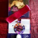 Foto con el contenido de sexo en todo el mundo: cinta de seda rosa sobre la caja del juego, ruleta sobre las castas/visados. Encima de la ruleta los dos dados: uno rosa y otro morado. Debajo de la ruleta, una velita blanca