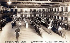 Foto en sepia donde se ve a hombres y mujeres en fila, todos con las manos en las caderas y una pierna estirada.