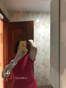 Foto delante del espejo del baño. La cara está tapada por el móvil y aparezco con camiseta corta roja y el codo doblado