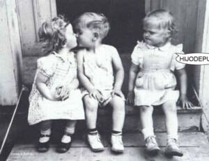 Foto en blanco y negro. Hay tres niños sentados. Dos niñas en los extemos y un niño en el centro. Mientras la niña de la izquierda de la foto besa al niño, la de la derecha los mira cabreada y tiene un bocadillo que dice: hijodepu