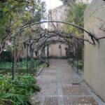 Pasillo del jardín donde se ve al fondo una estatua de la Celestina