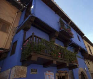 Calle del Chorrilo de Garganta de la Olla. Fachada azul de la casa de muñecas.
