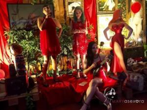 Actuación de las hermanas del desorden. Sobre el escenario, dos de las integrantes con vestidos rojos y sentada la tercera integrante