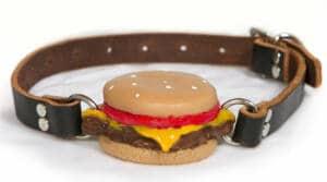 Mordaza de bdsm cuya bola silenciadora es una hamburguesa de silicona.