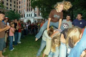 """Foto de varios jóvenes jugando a """"churro va"""". Una chica saltando y tres agachadas con la cabeza entre las piernas de la persona de delante."""