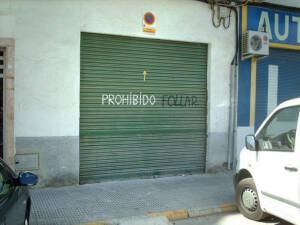Pintada en una puerta de garaje verde que pone en mayúsculas: Prohibido follar.