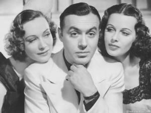 El actor Charles Boyer en el medio, mano en la barbilla. La actriz Sigrid Gurie, a la izquierda de la imagen, apoya su cabeza en el hombro de él mientras le mira. Al otro lado, Hedy Lamarr en identica posición.