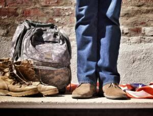 Foto de rodillas para abajo. Junto a las piernas, en el suelo, está una mochila de tipo camuflaje, unas botas de tipo militar y la bandera de EEUU.