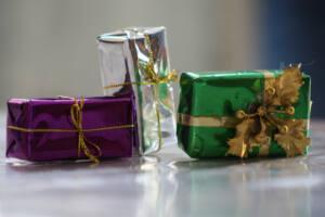 Tres cajas de regalo envueltas en distintos colores: morada, plata y verde