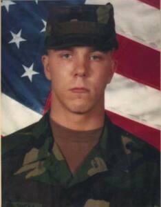 Foto oficial de Barry Winchel de uniforme con la bandera de los EEUU de fondo.