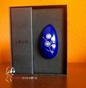 Estimulador azul con flor serigrafiada en blanco Nea 2 de LELO dentro de su caja priginal.