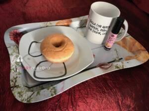 """En una bandeja aparece una taza de café con el mensaje: """"folla con quien quieras, pero que lea"""", un plato con un donut glaseado y el Lip gloss vibrant kiss sabor donut"""