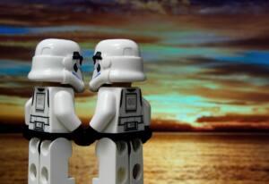 Dos stormtroope de Lego dándose la mano frente a una puesta de sol en la playa.