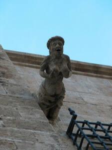 Gárgola de la catedral de Valencia. Una mujer desnuda con gesto lascivo que se toca los pechos.