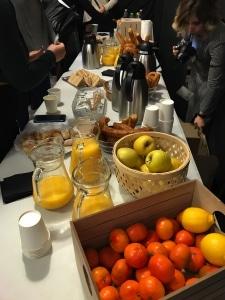 Panorámica de la mesa de desayuno The Sorority Van donde se ve: zumo, manzanas, mandarinas, churros, bollería, termos de café...