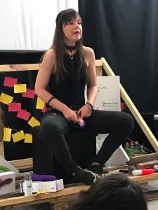 """Ana Lombardía en pleno taller de """"autocoñocimiento"""" con una vulva de tela explicando cómo es una vulva."""