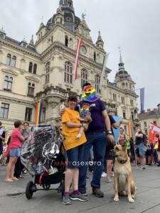 Foto de la familia completa, perro incluido frente al ayuntamiento de la ciudad de Graz. Padre e hijo tienen la cara enmascarada con un fantasma arcoíris.