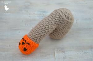 Calentador de pene realizado en hilo gris el tronco y testículos y con gorrito con forma de calazaba decorada en naranja y negro.