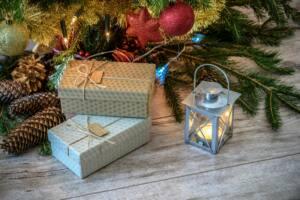 Dos cajas de regalo junto al pie de un árbol de Navidad