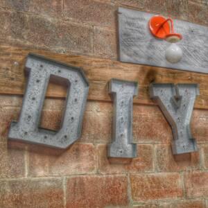 Siglas DIY en metal sobre pared de ladrillo